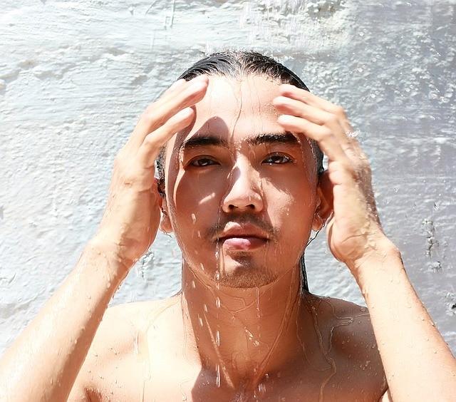 mężczyzna opłukuje wodą twarz